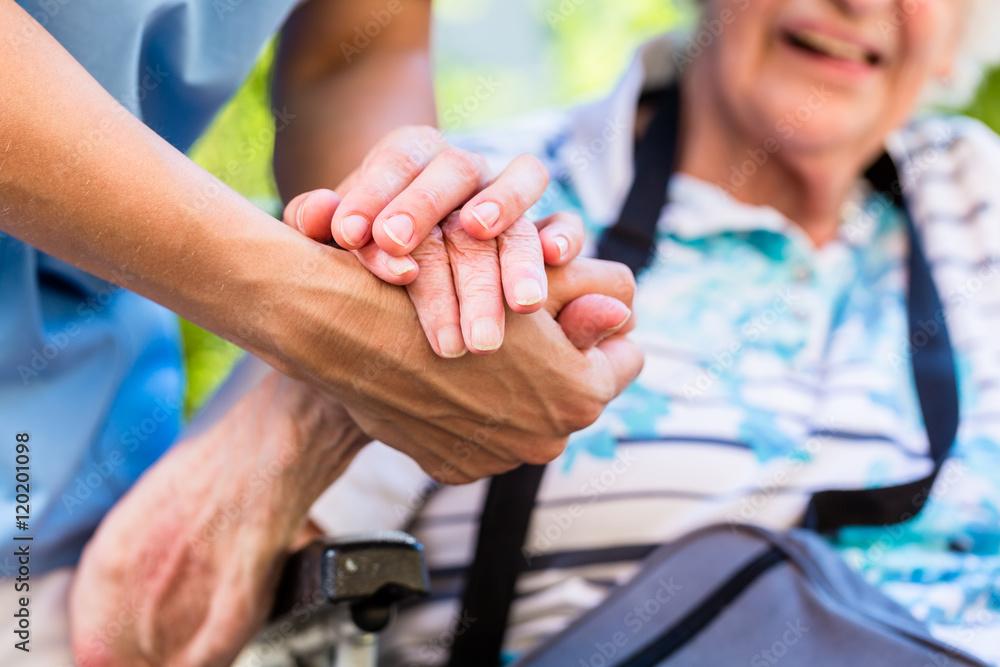 Fototapeta Nurse consoling senior woman holding her hand