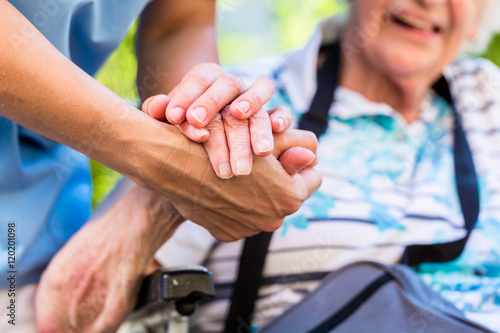 Obraz Nurse consoling senior woman holding her hand - fototapety do salonu