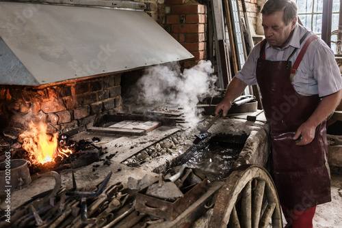 Blacksmith cooling work piece in water front of furnace fire