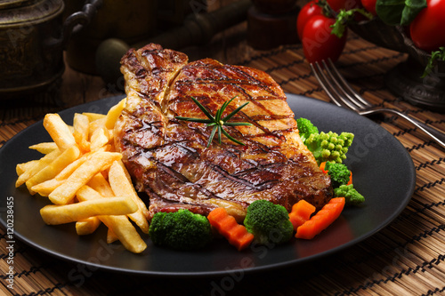 Papiers peints Steakhouse Grilled beef steak served with French fries and vegetables on a