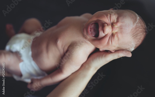 Foto  Portrait of newborn baby crying in parents' arms. Mother hands.