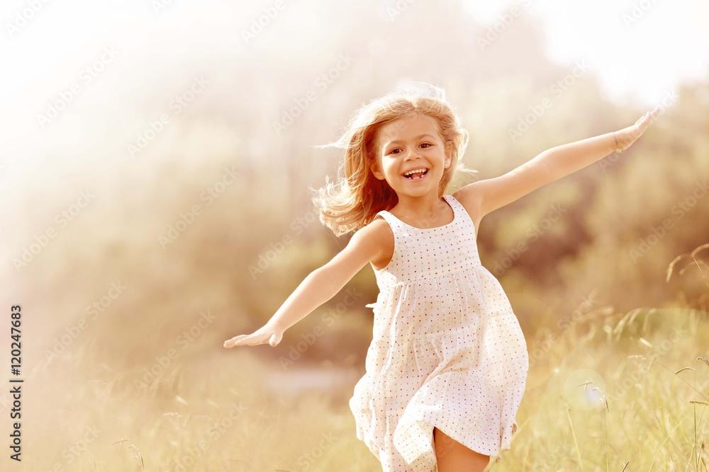 Fototapeta Little girl running in country field in summer