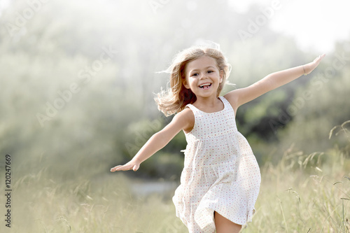 Photo Little girl running in country field in summer