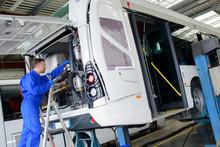 Mechanic Working On Engine Of Public Transport Bus