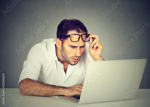Fotografía  man with glasses having eyesight problems confused with laptop