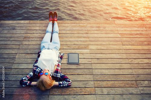 Fotografia  Top view young woman lying on a wooden jetty enjoying the sunshine
