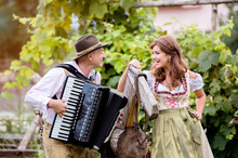 Couple In Traditional Bavarian Clothes With Accordion, Green Gar