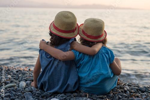 Fotografia  petites filles bras dessus bras dessous assises au bord de la mer