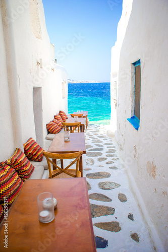 Fototapeten Schmale Gasse Benches with pillows in a typical greek bar in Mykonos with amazing sea view on Cyclades islands