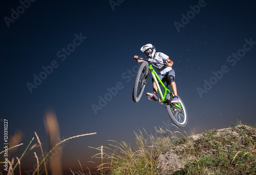 Carta da parati Young guy making high jump on a mountain bike on the hill against evening sky