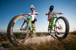 Two bikers wearing in helmets and glasses standing with the mountain bicycles on the slope under blue sky. Bottom view