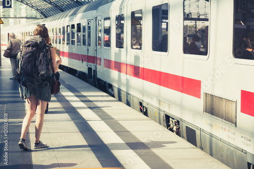 Girl with backpack at train station before entering train