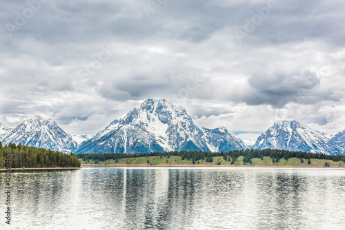 Photo  Grand Teton mountains with lake reflection and dark storm clouds overcast in nat