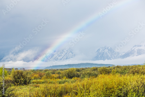 Photo  Grand Teton mountains covered with fog and dark storm clouds with rainbow