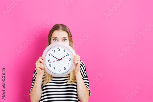Young woman holding a clock Fototapeta
