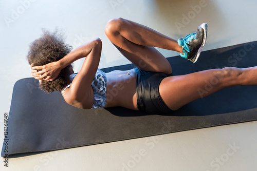 Fotografie, Obraz  smiling young woman working out at fitness center doing crunch a
