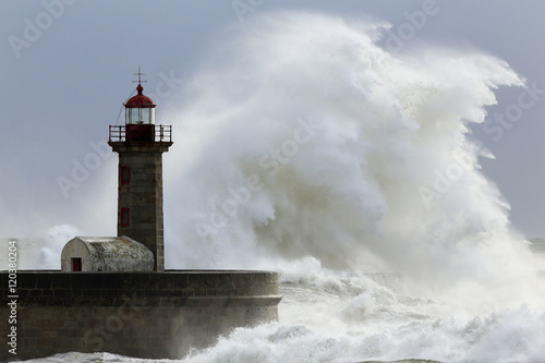 Photo sur Toile Phare Big stormy wave in a sunnjy day