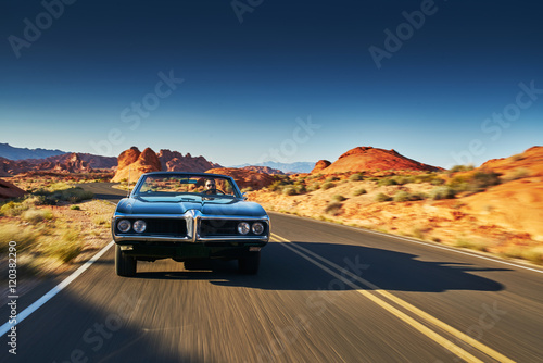 Foto man driving vintage car through desert