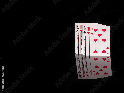 Платно  Three of a Kind playing cards isolated on black background.