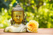 Chinese buddha sculpture and yellow rose flower on natural blur green background. Spa concept. Calmness and tranquility. Copy space.