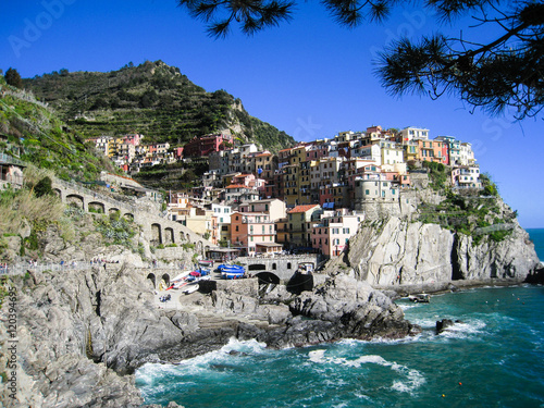 Foto op Aluminium Kust Colorful houses on cliff, Manarola, blue sea