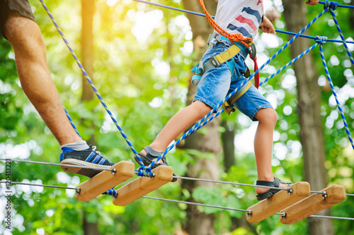 Fotografía  A child accompanied by an adult moves on ropes course