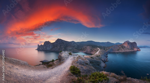 Staande foto Nachtblauw Beautiful panoramic landscape with mountains, sea, blue sky and beautiful colorful red clouds at sunset in Crimea. Sunset in mountains. Path in rock. Nature background. Vibrant landscape in twilight.