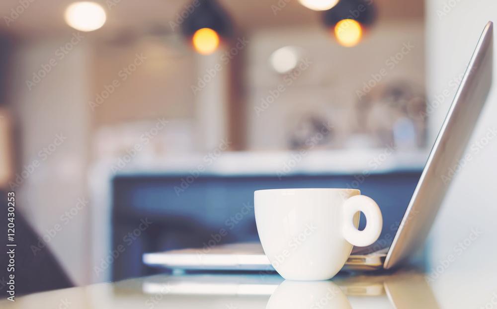 Laptop computer beside coffee mug