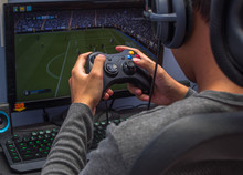 Back View Of Young Gamer Playing Video Game Wearing Headphone Using His Controller.
