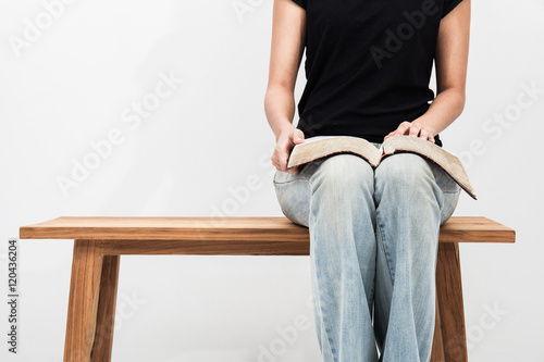 Casual young woman holds an open Bible on her lap. Canvas Print