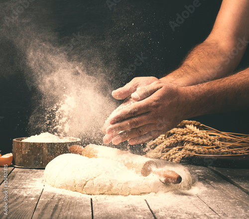 Obraz na plátne Man preparing bread dough on wooden table in a bakery