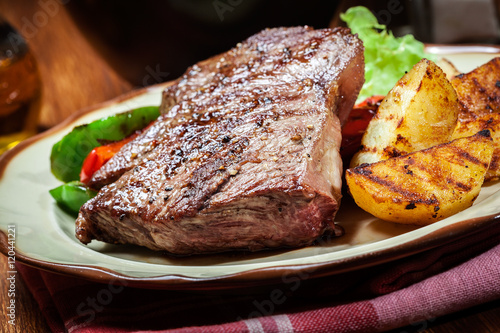 Fotografie, Obraz  Portions of grilled beef steak with grilled potatoes and paprika