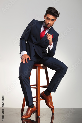 serious business man in elegant double breasted suit sitting Poster
