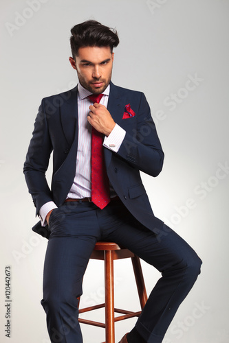 seated elegant business man fixing his tie Poster