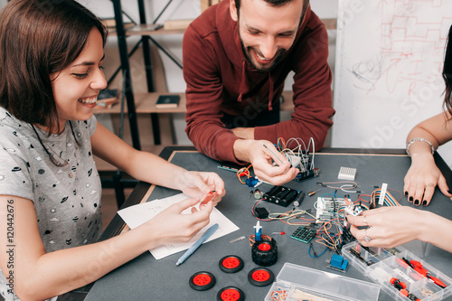 Laughing engineers at workplace, successful experiment concept. Young creative team of scientists satisfied and smiling, sitting at laboratory with electronic components and equipment