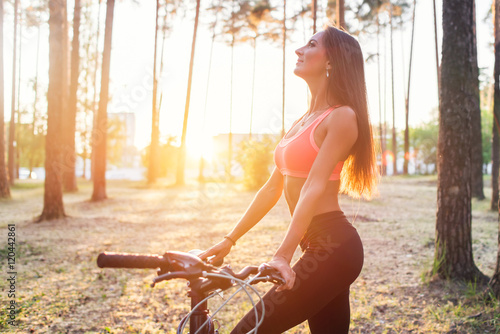 Fit woman standing with bicycle in park enjoying sunset.