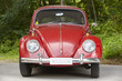 Red european classic car over a green forest background