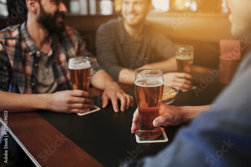 Fototapeta happy male friends drinking beer at bar or pub obraz