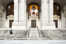 Distant View Of Businesswoman Sitting At New York Public Library Entrance