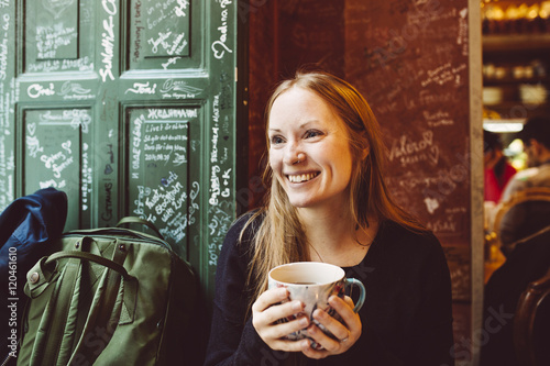 Sweden, Stockholm, Gamla Stan, Smiling woman holding coffee cup in cafe Poster