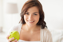 Smiling Young Woman Eating Green Apple At Home