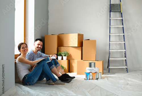 Young happy couple sitting floor in the new home Canvas-taulu