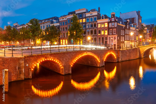Photo Amsterdam canal Reguliersgracht, bridge and typical houses, boats and bicycles during evening twilight blue hour, Holland, Netherlands