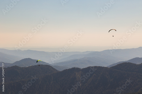 Spoed Fotobehang Luchtsport Paragliders flying over mountains