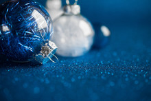 White And Blue Christmas Ornaments On Dark Blue Glitter Background With Space For Text. Merry Christmas Card. Winter Holidays. Xmas Theme. Happy New Year. Space For Text.