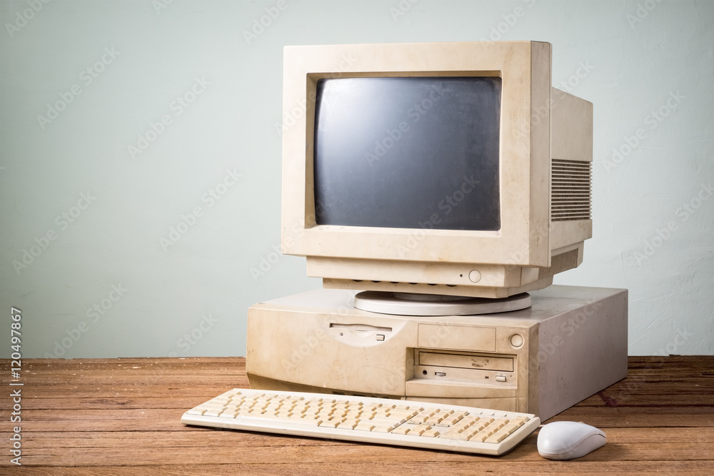 Fototapety, obrazy: old and obsolete computer on old wood table with concrete wall background