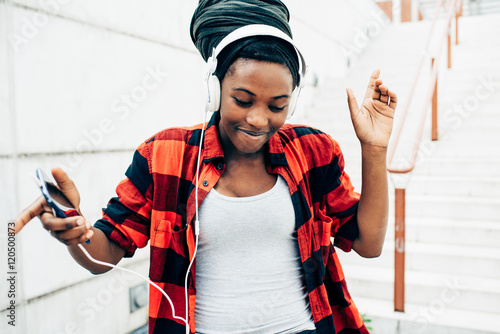 Valokuva  Half lenght of young beautiful afro black woman listening musi with head phones