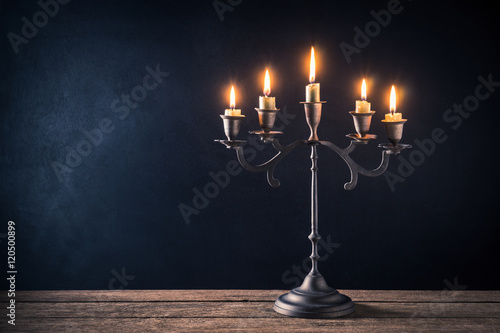 Foto handicraft candelabrum with burning candles on old wooden table against art dark