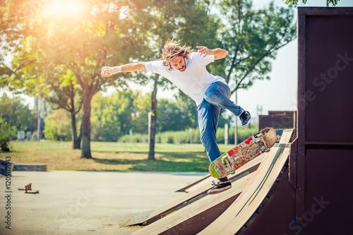Plakat Młody człowiek jazdy na łyżwach w parku i spada w dół