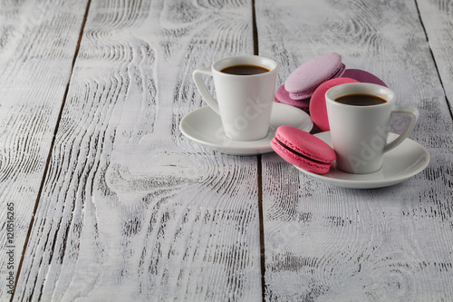Two cups of black coffee with a delicious macaroons